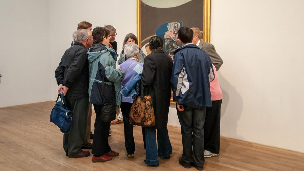 mensen kijken naar een schilderij
